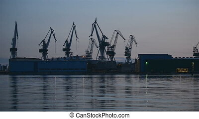 Industrial cargo cranes in the dock at sunset