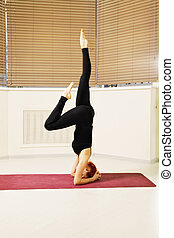 Head stand - Redhead exercising head stand pose one leg...