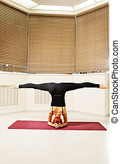 Head stand legs stretched - Redhead exercising head stand...