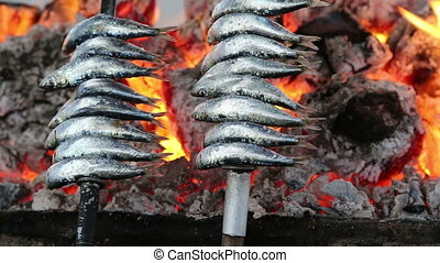 Cooking fish grilled over hot coals bonfire