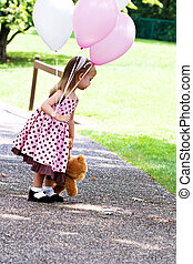 Child with balloons - Little girl at a park with pink and...