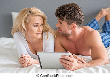 Couple Lying in Bed Arguing While Using Tablet - Young White...