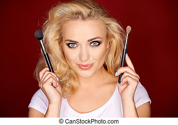 Female holding up makeup brush - Lovely young female holding...
