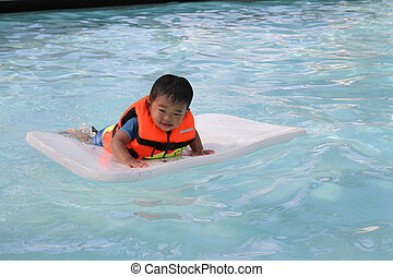Japanese boy swimming in the pool