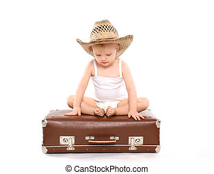 Little child in a straw summer hat sitting on the suitcase,...