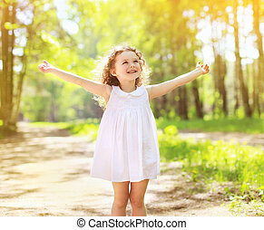 Positive charming curly little girl enjoying summer sunny...