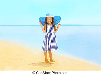 Fashion little girl in a striped dress and hat relaxing on the b