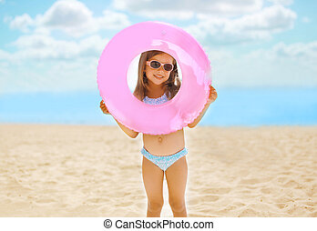 Positive child with inflatable circle on the beach having fun