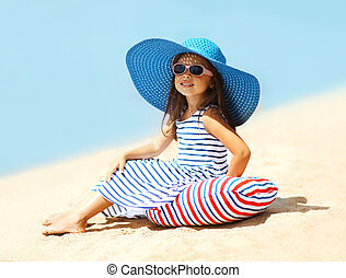Pretty little girl in a striped dress and hat relaxing on the be