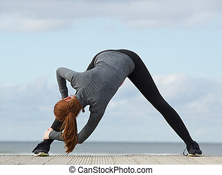 Sporty woman bending down and stretching exercise - Young...