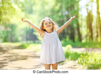 Charming little girl enjoying summer sunny day, raises his...