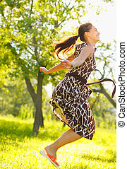 Free time - Young beautiful woman jumping in a meadow