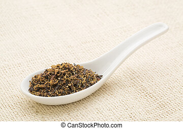 Irish moss seaweed on a white Chinese spoon against burlap...