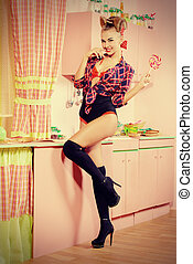 sweets lover - Pretty pin-up girl posing on a pink kitchen...