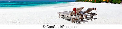 Christmas beach vacation - Panorama of two sun loungers with...