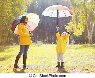 Family with colorful umbrella having fun enjoying weather in...