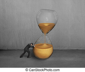 male hand push tilt hour glass with concrete wall
