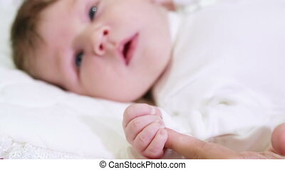 Lying baby holds hands her mother - Baby carelessly lying on...