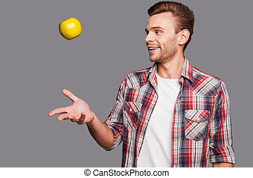 Juggling his healthy lifestyle. A smiling man throwing an...