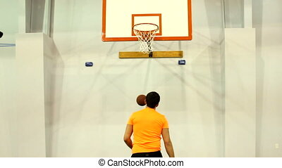 Basketball Practice - Player shoots basketball hoops during...