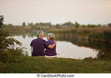 Happy senior couple sitting in summer near lake during...