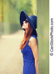 Redhead girl in sunglasses near fence in Versailles garden