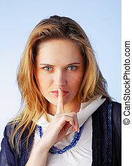 Shhh...... - Beautiful young woman with her finger to her...