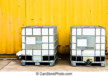White container and yellow cargo - White IBC container in...