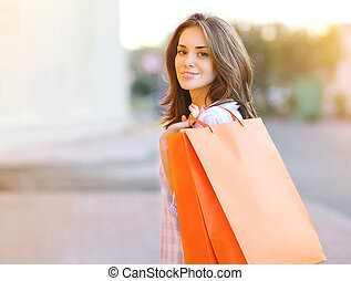 Pretty smiling woman with shopping bags, lifestyle casual...
