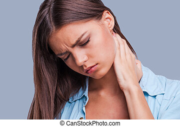 Woman with neck pain. Young woman holding her aching neck...