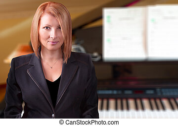 Piano Teacher - Piano teacher with her piano in the back.