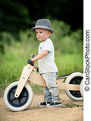Little boy with tricycle in nature - Little boy with wooden...