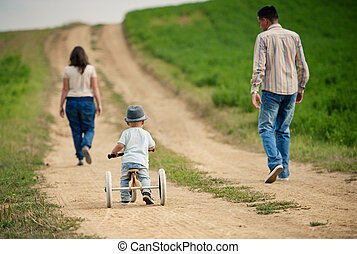 Family with little boy on tricycle in nature - Happy family...