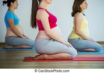 Pregnant women exercising - Group of young pregnant women...