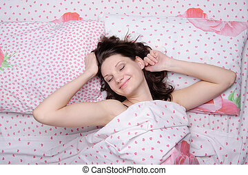 young girl waking up in bed happily stretches