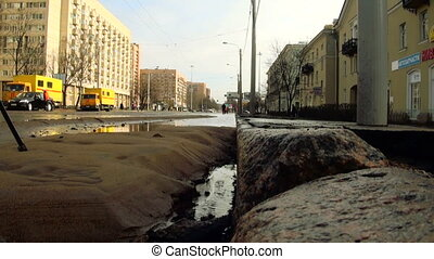 Water flows out from under the asphalt. The accident rupture of the pipeline.