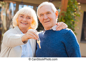 Happy seniors. Happy senior couple bonding to each other and smiling while woman holding keys in her hand