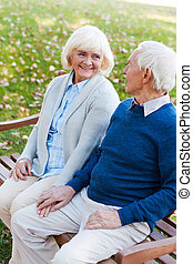 Relaxing in park together. Top view of happy senior couple holding hands and looking at each other while sitting on the bench in park together