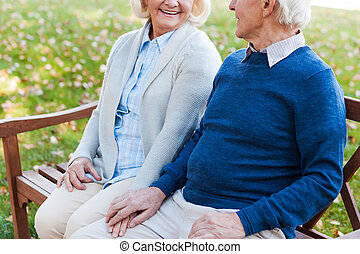 Enjoying their time together. Close-up of happy senior couple holding hands and looking at each other while sitting on the bench in park together