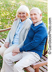 Enjoying each other. Top view of happy senior couple holding hands and looking at camera with smile while sitting on the park bench together