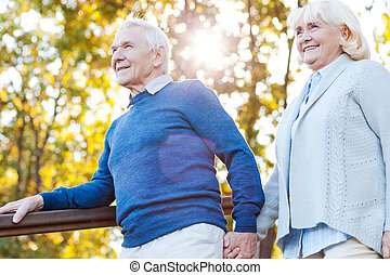 Enjoying beautiful day together. Happy senior couple holding...