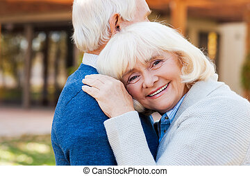 Love forever. Happy senior woman leaning at shoulder of her...