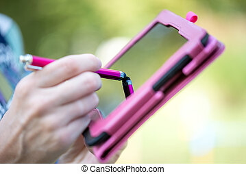 Woman writing on a tablet with a stylus - Close up view of...