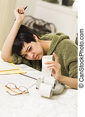 Multi-ethnic Young Woman Agonizing Over Financial...
