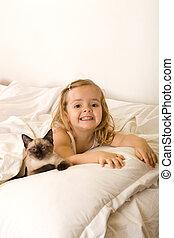 Little girl relaxing with her kitten