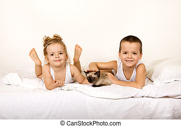Kids with their kitten on the bed