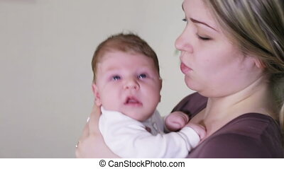Mum with child - Young mother kissing her son and playing...
