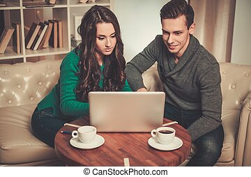 Young couple with laptop and coffee behind table