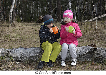 Spring in the woods sitting on a log and small children...