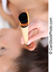 Ear candling, natural purifying - Woman relaxes in the study...